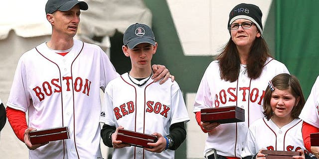 BOSTON - APRIL 4: The Boston Red Sox 2013 World Series team received their championship rings during a pre-game ceremony before their home opener at Fenway Park against the Milwaukee Brewers on Friday, April 4, 2014. Family members of Boston Marathon bombing victim Martin Richard, sister Jane Richard at right, carried the rings onto the field along with others who were affected by the tragedy. (Photo by Jim Davis/The Boston Globe via Getty Images)