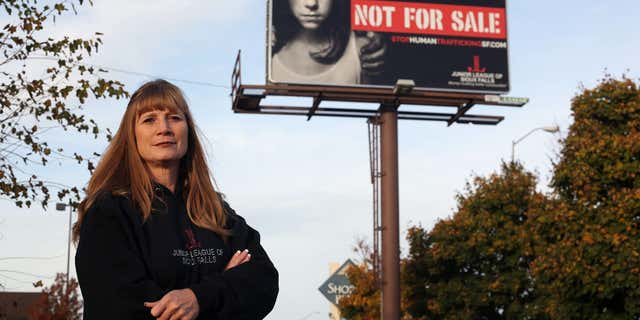 In this Oct. 27, 2015 photo, Dawn Stenberg, from the Junior League of Sioux Falls, stands near the group's anti-human trafficking billboard in Sioux Falls, S.D.