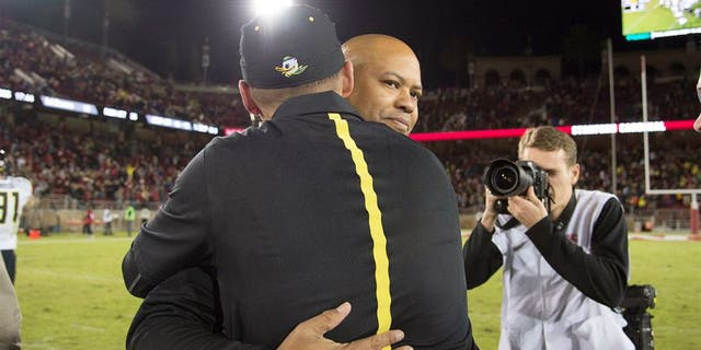 November 14, 2015; Stanford, CA, USA; Stanford Cardinal head coach David Shaw hugs Oregon Ducks head coach Mark Helfrich after the game at Stanford Stadium. The Ducks defeated the Cardinal 38-36. Mandatory Credit: Kyle Terada-USA TODAY Sports