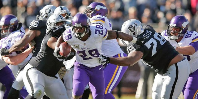 OAKLAND, CA - NOVEMBER 15: Running back Adrian Peterson #28 of the Minnesota Vikings breaks through the takcle against the Oakland Raiders in the first quarter at O.co Coliseum on November 15, 2015 in Oakland, California. (Photo by Ezra Shaw/Getty Images)