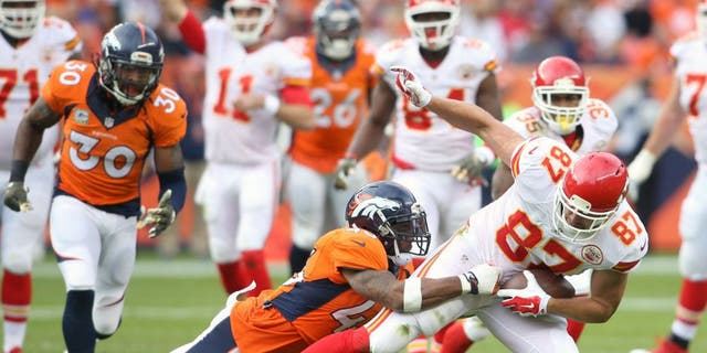Nov 15, 2015; Denver, CO, USA; Kansas City Chiefs tight end Travis Kelce (87) is brought down by Denver Broncos strong safety T.J. Ward (43) after catching a pass during the first half at Sports Authority Field at Mile High. Mandatory Credit: Chris Humphreys-USA TODAY Sports