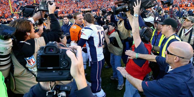 Jan 19, 2014; Denver, CO, USA; Members of the media fight for position to photograph Denver Broncos quarterback Peyton Manning shaking hands with New England Patriots quarterback Tom Brady following the 2013 AFC Championship football game at Sports Authority Field at Mile High. Mandatory Credit: Mark J. Rebilas-USA TODAY Sports