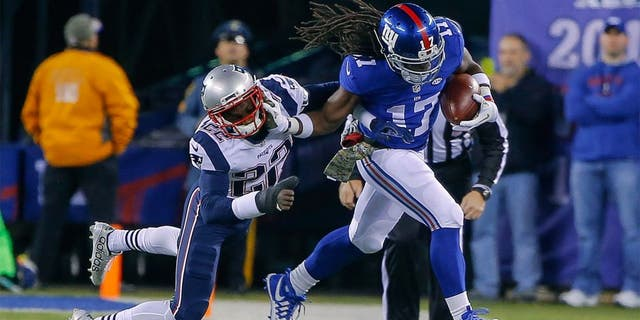 Nov 15, 2015; East Rutherford, NJ, USA; New York Giants wide receiver Dwayne Harris (17) stiff arms New England Patriots cornerback Justin Coleman (22) after a reception during the second quarter at MetLife Stadium. Mandatory Credit: Jim O'Connor-USA TODAY Sports