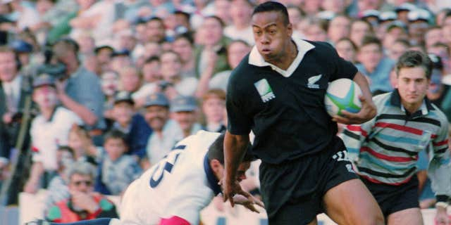 In this June 18, 1995 file photo, New Zealand All Blacks winger Jonah Lomu runs around England's Will Carling on his way to score the opening try in the Rugby World Cup semifinal at Newlands in Cape Town, South Africa.