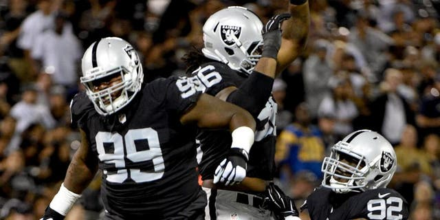 August 14, 2015; Oakland, CA, USA; Oakland Raiders defensive tackle Leon Orr (99), defensive end Denico Autry (96), and defensive tackle Stacy McGee (92) celebrate during the fourth quarter in a preseason NFL football game against the St. Louis Rams at O.co Coliseum. The Raiders defeated the Rams 18-3. Mandatory Credit: Kyle Terada-USA TODAY Sports