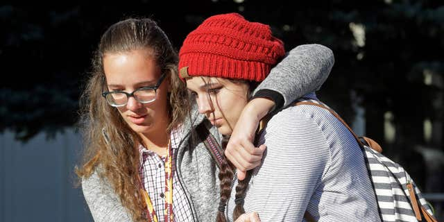 Students Albany Cox, right, and Holly Hilton leave Mountain View High School where several students were stabbed Tuesday, Nov. 15, 2016, in Orem, Utah.