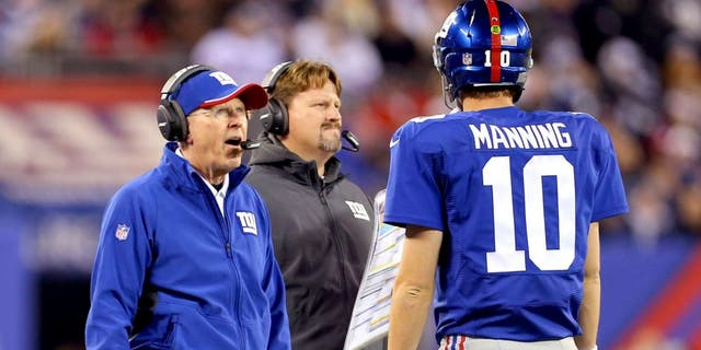 Nov 23, 2014; East Rutherford, NJ, USA; New York Giants head coach Tom Coughlin and offensive coordinator Ben McAdoo talk with quarterback Eli Manning (10) during a break in play against the Dallas Cowboys during the second quarter at MetLife Stadium. Mandatory Credit: Adam Hunger-USA TODAY Sports