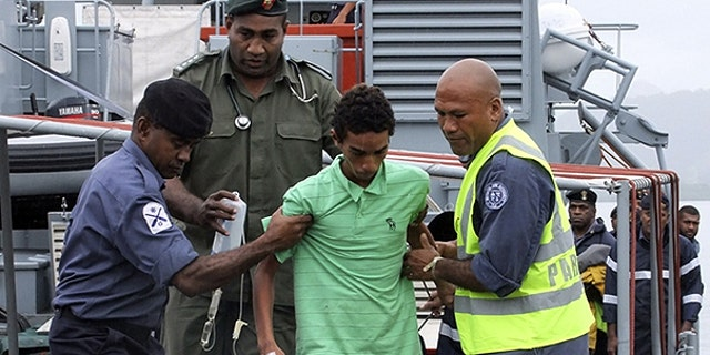 Nov. 26: One of three boys from Tokelau island, center, is helped on his arrival at the Stanley Brown Naval Base in Suva, Fiji.
