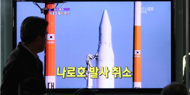 Nov. 29, 2012: People watch a TV broadcasting a report about the cancellation of a launch of the Korea Space Launch Vehicle-1, at Seoul Railway Station in Seoul, South Korea.