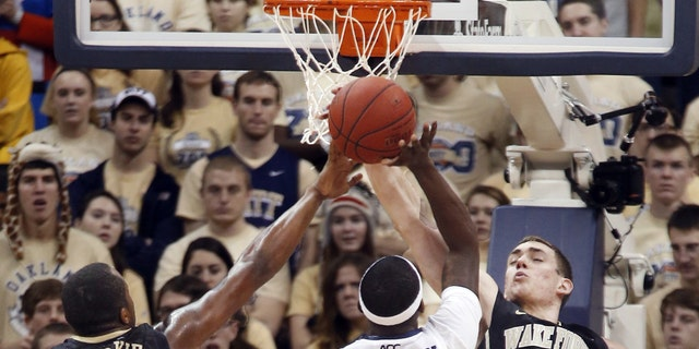 Wake Forest's Travis McKie (30) and Tyler Cavanaugh (34) combine to block a shot by Pittsburgh's Durand Johnson (5) in the second half of an NCAA college basketball game on Saturday, Jan. 11, 2014, in Pittsburgh. (AP Photo/Keith Srakocic)