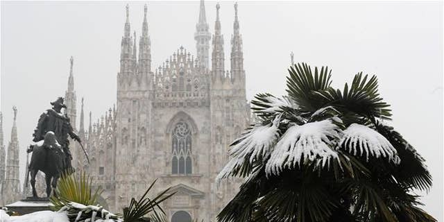 Palm trees are dusted in snow in front of Milan's Gothic Cathedral, Italy, on March 2, 2018.
