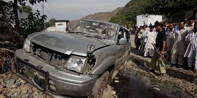 November 8, 2011: People look at a vehicle targeted by a suicide attacker in Swabi near Peshawar, Pakistan.