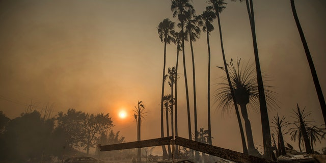 Smoke rises behind a leveled apartment complex as a wildfire burns in Ventura, California, Tuesday.