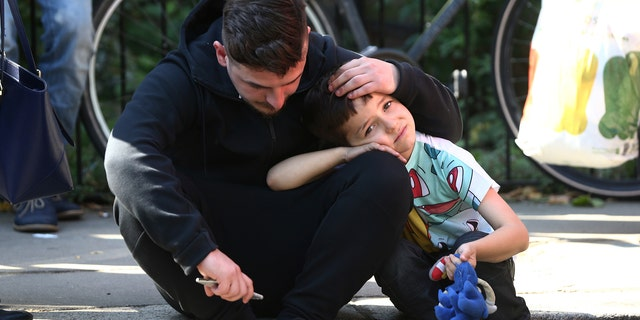 A man comforts a boy after a tower block was severly damaged by a serious fire, in north Kensington, West London, Britain June 14, 2017. REUTERS/Neil Hall - RTS1702W