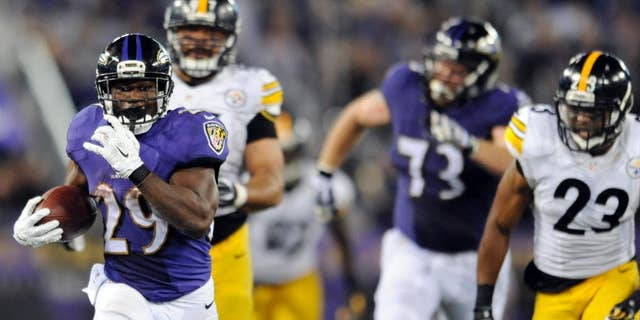 Baltimore Ravens running back Justin Forsett (29) runs away from Pittsburgh Steelers defensive end Cameron Heyward (97) and free safety Mike Mitchell (23) during the second half of an NFL football game Thursday, Sept. 11, 2014, in Baltimore. The Ravens won 26-6. (AP Photo/Gail Burton)
