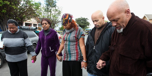 Members of the neighborhood are led in prayer from Pastor Joyce Williams, second from left, at the site of a drowning Wednesday Feb.  15, 2012 in Los Angeles. A Los Angeles mother has been detained after the drowning death of a 1-year-old girl and the critical injury of a 5-year-old girl. (AP Photo/Nick Ut)