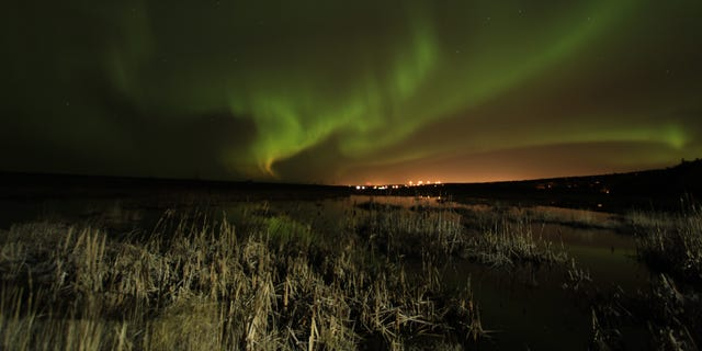 Northern lights (aurora borealis) illuminate the sky over Potter Marsh, foreground, and in the distance, Anchorage, Alaska, on Saturday, Oct. 13, 2012 shortly after midnight. (AP Photo/Dan Joling)
