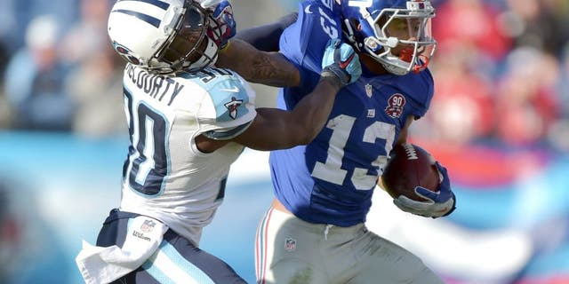 Dec 7, 2014; Nashville, TN, USA; New York Giants wide receiver Odell Beckham Jr (13) carries the ball against Tennessee Titans cornerback Jason McCourty (30) during the second half at LP Field. The Giants beat the Titans 36-7. Mandatory Credit: Don McPeak-USA TODAY Sports