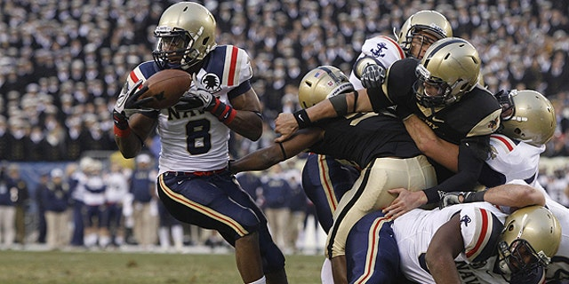 Dec. 11: Navy safety Wyatt Middleton, left, grabs a loose ball from Army quarterback Trent Steelman, right, in the first half of an NCAA college football game, in Philadelphia.