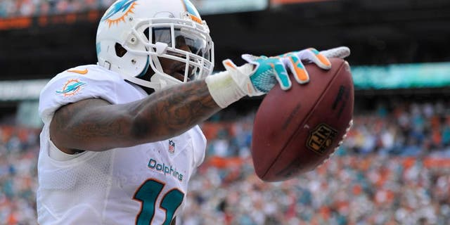 Dec 15, 2013; Miami Gardens, FL, USA; Miami Dolphins wide receiver Mike Wallace (11) celebrates his touchdown against the New England Patriots in the first half of the game at Sun Life Stadium. Mandatory Credit: Brad Barr-USA TODAY Sports