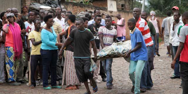 Dec. 12, 2015: Men carry away a dead body in the Nyakabiga neighborhood of Bujumbura, Burundi.