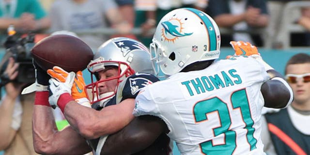 New England Patriots wide receiver Danny Amendola (80) attempts to hold onto the ball as Miami Dolphins Michael Thomas (31) defends during the second half of an NFL football game, Sunday, Dec. 15, 2013, in Miami Gardens, Fla. The Dolphins defeated the Patriots 24-20. (AP Photo/J Pat Carter)