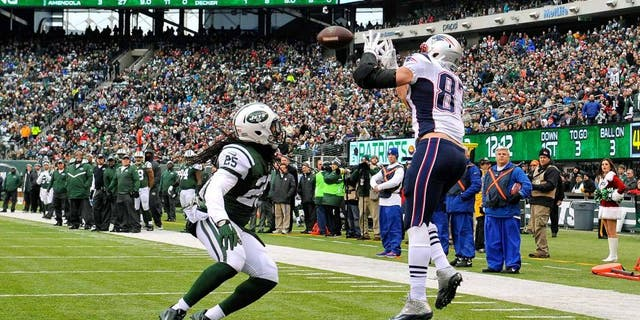 EAST RUTHERFORD, NJ - DECEMBER 21: Tight end Rob Gronkowski #87 of the New England Patriots catches a touchdown in the second quarter as free safety Calvin Pryor #25 of the New York Jets defends during a game at MetLife Stadium on December 21, 2014 in East Rutherford, New Jersey. (Photo by Alex Goodlett/Getty Images)