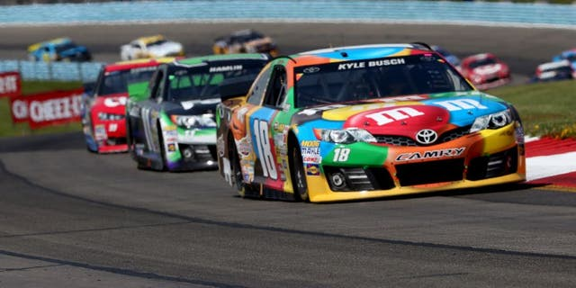 WATKINS GLEN, NY - AUGUST 10: Kyle Busch, driver of the #18 M&M's Toyota, leads a pack of cars during the NASCAR Sprint Cup Series Cheez-It 355 at Watkins Glen International on August 10, 2014 in Watkins Glen, New York. (Photo by Mark Wilson/Getty Images)