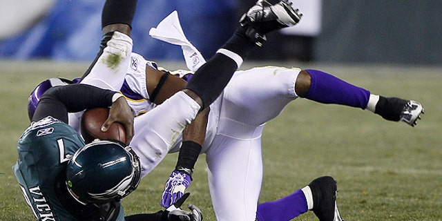 Dec. 28: Philadelphia Eagles quarterback Michael Vick, left, tumbles after a tackle by Minnesota Vikings cornerback Antoine Winfield in the first half of an NFL football game in Philadelphia.