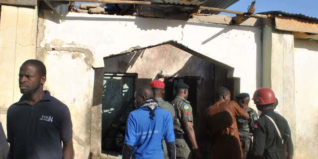 dec. 28, 2015: People gather at a damaged building following an attack by Boko Haram in Maiduguri, Nigeria
