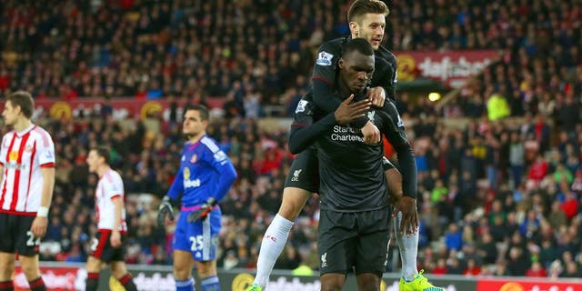 SUNDERLAND, ENGLAND - DECEMBER 30: Christian Benteke of Liverpool celebrates with team-mate Adam Lallana of Liverpool after scoring the opening goal as Sunderland players show their dejection during the Barclays Premier League match between Sunderland and Liverpool at Stadium of Light on December 30, 2015 in Sunderland, England. (Photo by Ian MacNicol/Getty Images)