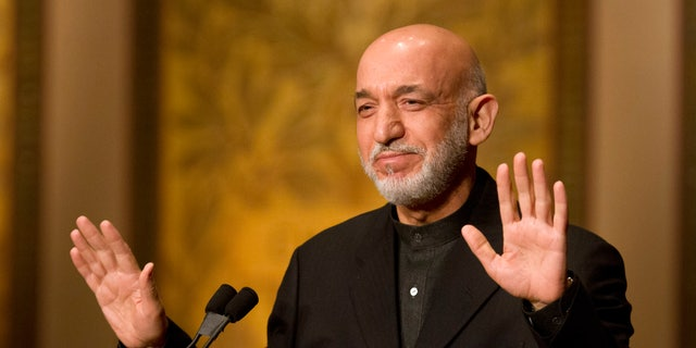 Afghanistan President Hamid Karzai gestures for applause to stop before he began his speech at Georgetown University in Washington, Friday, Jan. 11, 2013. (AP Photo/Jacquelyn Martin)