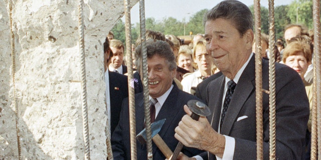 "Former U.S. President Ronald Reagan holding a hammer and chisel next to the Berlin Wall on Poltsdammer Platz in East Berlin in 1990. In Berlin in 1987, Reagan challenged Soviet leader Mikhail Gorbachev to ""tear down this wall,"" but later developed a warm relationship with his former adversary. REUTERS/Michael Probst/Files JDP - RTR3RSA"