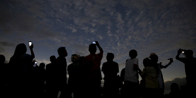 People watch and take pictures of the solar eclipse at the beach on Ternate island, Indonesia, March 9, 2016.  REUTERS/Beawiharta      TPX IMAGES OF THE DAY      - RTS9XDW