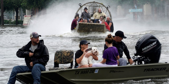 People are rescued from flood waters from Hurricane Harvey on an air boat in Dickinson, Texas August 27, 2017.