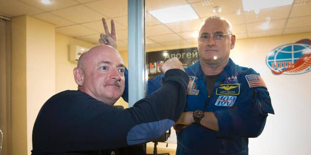 U.S. astronaut Scott Kelly, right, crew member of the mission to the International Space Station, ISS, poses through a safety glass with his brother, Mark Kelly, after a news conference in Russian leased Baikonur cosmodrome, Kazakhstan, Thursday, March 26, 2015.