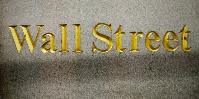 FILE - In this Oct. 8, 2014, file photo, a Wall Street address is carved in the side of a building in New York. European stocks drifted sideways, Tuesday, Feb. 24, 2015, as investors awaited remarks from U.S. Federal Reserve Chair Janet Yellen to glean any hints on when interest rates might go up. (AP Photo/Mark Lennihan, File)