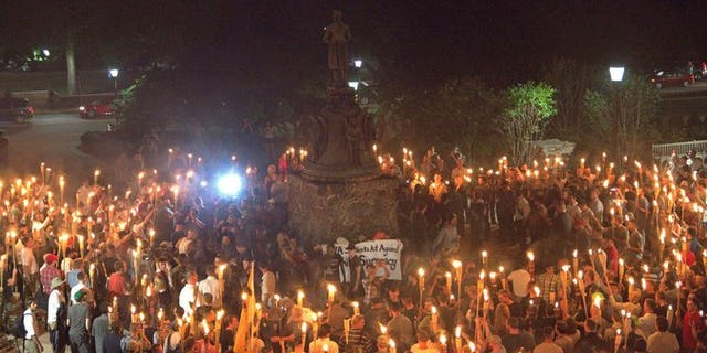 "White nationalists gathered around a statute of Robert E. Lee at the University of Virginia campus on Aug. 11, 2017 bearing tiki torches and shouting slogans like ""Jews will not replace us"" and ""White lives matter."""