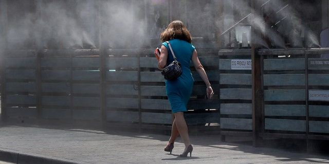 A woman walks along a row of misters Monday, June 19, 2017 in Tempe, Ariz. The forecast calls for a high of 118 on Monday and 120 on Tuesday in Phoenix.  (AP Photo/Matt York)