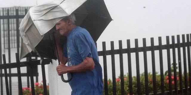 A man carrying an umbrella walks on a street as Hurricane Irma howls past Puerto Rico after thrashing several smaller Caribbean islands, in Fajardo, Puerto Rico September 6, 2017.  REUTERS/Alvin Baez - RC147BEAFC70