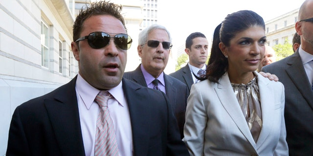 """Giuseppe """"Joe"""" Giudice, 43, left, and his wife, Teresa Giudice, 41, of Montville Township, N.J., walk out of Martin Luther King, Jr. Courthouse after a court appearance, Tuesday, July 30, 2013, in Newark, N.J."""