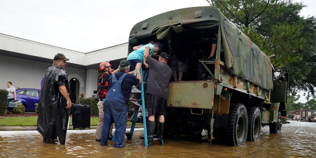 Volunteers load people into a collector's vintage military truck to evacuate them from flood waters from Hurricane Harvey in Dickinson, Texas, U.S. August 27, 2017.