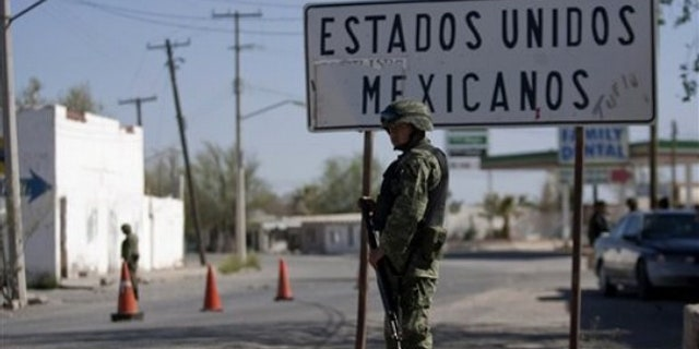 In this photo taken April 7, 2010, soldiers guard near the U.S.-Mexico border in Caseta border town, Valle de Juarez, northern Mexico. Hundreds of families are fleeing the cotton-farming towns of the Juarez Valley, a stretch of border 50 miles east of Ciudad Juarez. In a new strategy, Mexican drug cartels seeking to minimize interference with their operations are using terror to empty the entire area. (AP Photo/Guillermo Arias)