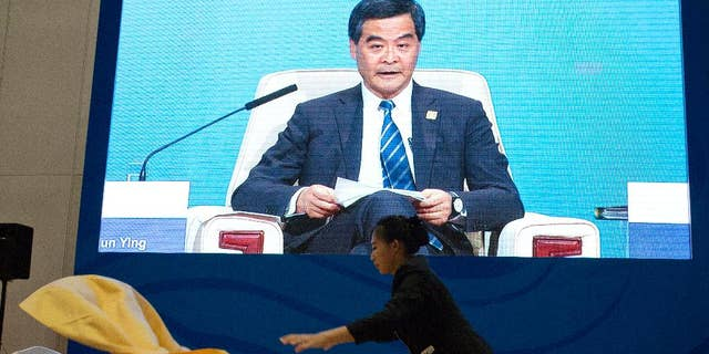 A Chinese waitress lays out a table cloth as Hong Kong's Chief Executive Leung Chun-ying appears on a live broadcast at a dining area of the media center for the Asia-Pacific Economic Cooperation (APEC) Economic  meetings held in Beijing, China, Sunday, Nov. 9, 2014. (AP Photo/Ng Han Guan)