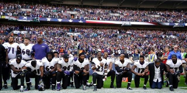 Baltimore Ravens players, including former player Ray Lewis, second from right, kneel down during the playing of the U.S. national anthem before an NFL football game against the Jacksonville Jaguars at Wembley Stadium in London on Sunday.