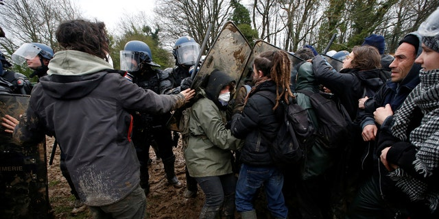 Protesters try to block French gendarmes during an evacuation operation.
