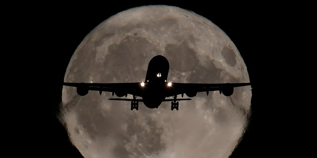 A passenger plane, with a full Harvest moon seen behind, makes its final landing approach towards Heathrow Airport in London, Britain, October 5, 2017 - file photo. REUTERS/Toby Melville