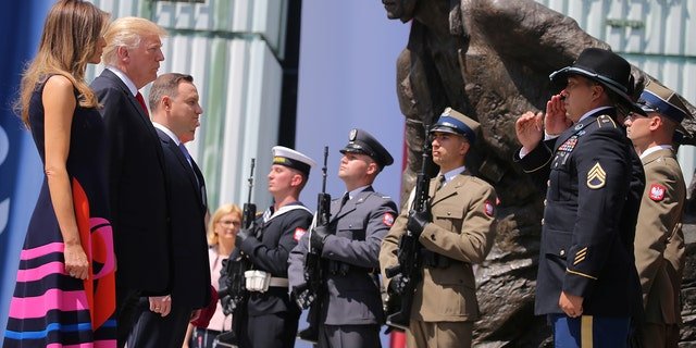 U.S. President Donald Trump, First Lady of the U.S. Melania Trump and Polish President Andrzej Duda stand in front of the Warsaw Uprising Monument at Krasinski Square, in Warsaw, Poland July 6, 2017. REUTERS/Carlos Barria     TPX IMAGES OF THE DAY - RTX3AA2L