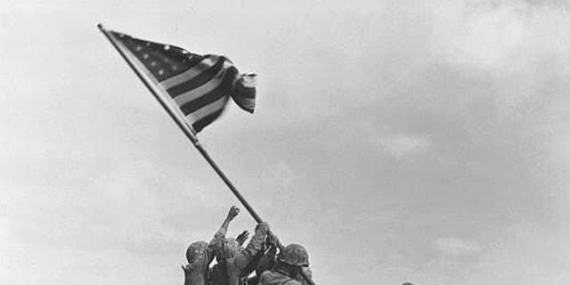 U.S. Marines of the 28th Regiment, 5th Division, raise the American flag atop Mt. Suribachi, Iwo Jima, on Feb. 23, 1945. (Joe Rosenthal/Associated Press)