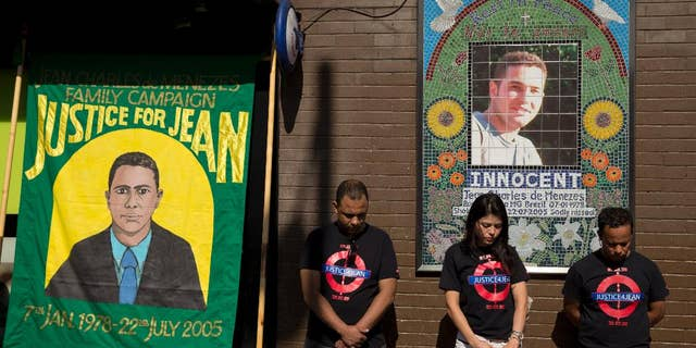 FILE - In this Wednesday, July 22, 2015 file photo, cousins Alessandro Pereira, right, Vivian Figueiredo and friend Erionaldo da Silva, left, observe a minute's silence on the 10-year-anniversary of the death of 27-year-old Brazilian electrician Jean Charles de Menezes, shot by British police, at Stockwell station in London. A European court on Wednesday, March 30, 2016 says British authorities were right not to prosecute police officers over the killing of a Brazilian man shot on the London Underground after being mistaken for a suicide bomber. The judgment by the European Court of Human Rights is a blow to relatives of Jean Charles de Menezes, who have sought for years to have police charged with his slaying. (AP Photo/Matt Dunham, file)